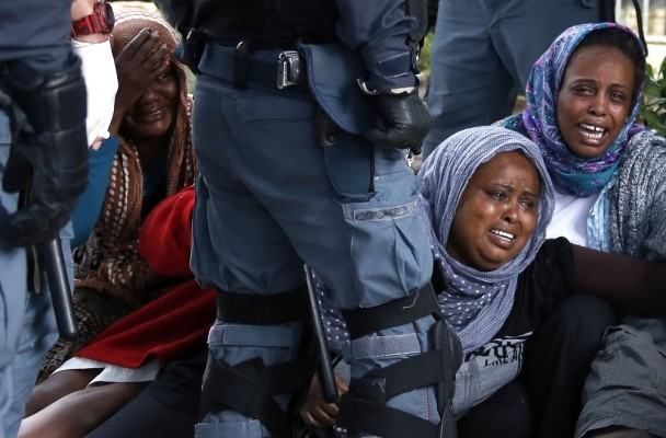A group of migrants react as they are evacuated by Italian police from the Saint Ludovic border crossing on the Mediterranean Sea between Vintimille, Italy and Menton, France, June 16, 2015. On Saturday,some 200 migrants, principally from Eritrea and Sudan, attempted to cross the border from Italy and were blocked by Italian police and French gendarmes.   REUTERS/Eric Gaillard   - RTX1GOIU